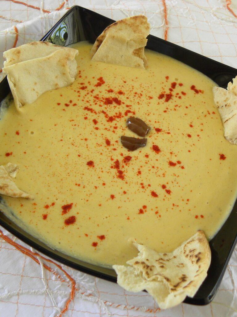 Χούμους ντιπ σε μαύρο πιάτο με ελιές και πίτα εικόνα