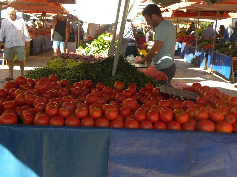 Ντομάτες και πωλητής σε πάγκο Λαϊκής αγοράς εικόνα